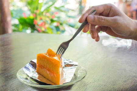 One hands reach to slice orange cake with fork photo
