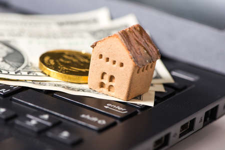 The cash and gold with the house model on laptop, the business finance and technology concept