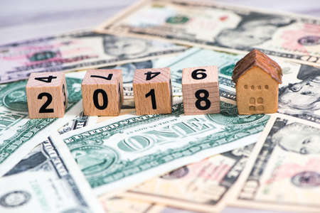 2018 new year cubes with the house model on group of cash, the business finance and property concept  business, money, finance, wealth, investment, plan, economy, banking, credit, account, statement, passbook, success, salary, concept, family, currency, g Editorial