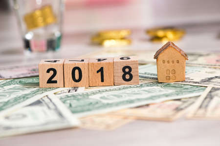 2018 new year cubes with the house model on group of cash, the business finance and property concept Stock Photo