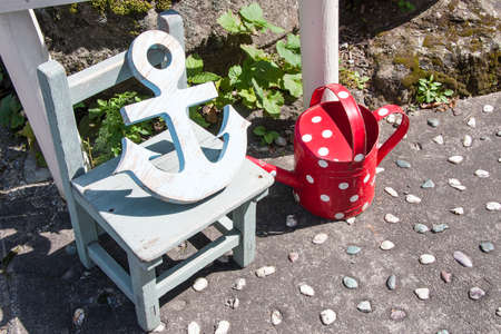 Anchor, wooden chair and watering can photo