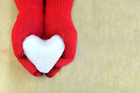 Snow heart in red gloves on wooden surface