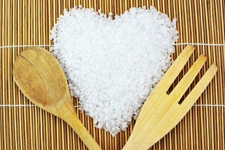Sea salt in heart shape with a spoon and fork on mats background
