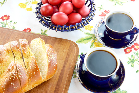 Easter bread , red eggs and cups of coffee on floral tablecloth Stock Photo