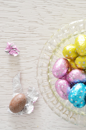 Chocolate egg foil wrapper and chocolate egg beside a glass bowl with foil wrapped Chocolate on white wooden table