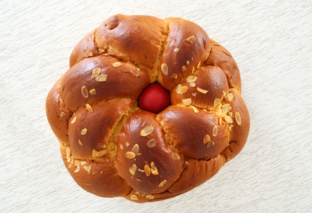 Traditional Easter bread ,tsoureki with red egg in the middle on white wooden background
