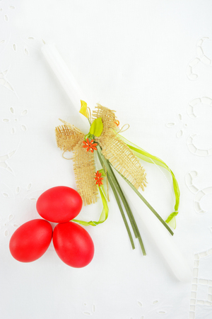 Easter candle and red eggs  on white linen tablecloth