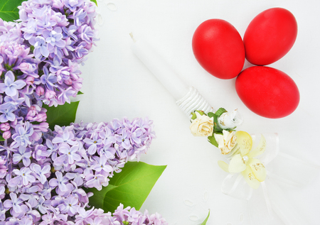 Lilac , Easter candle and red eggs on white linen tablecloth