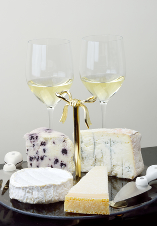 Platter with camembert, parmigiano, gorgonzola and white stilton with blueberries, pointed fork , spade-shaped knife and two glasses white wine