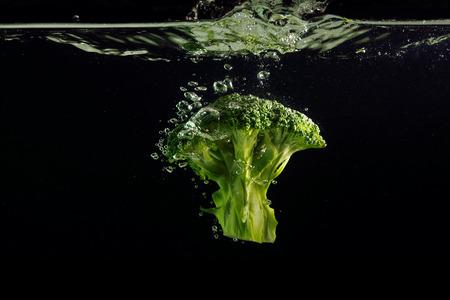 Broccoli splash on black background 版權商用圖片 - 95123552