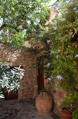 Stone house through tree and plants in Monemvasia Фото со стока