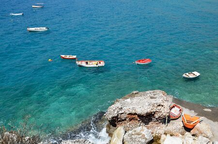 Small fishing boats floating in blue waters