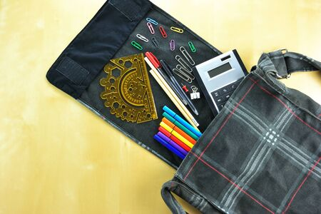 Bag and scool supplies on wooden background