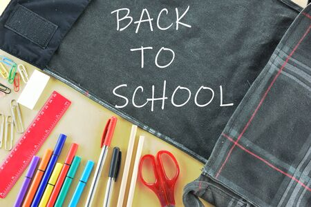 Back to school concept with bag and school supplies on wooden background