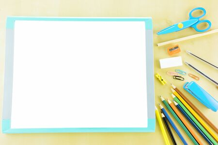 Blank whitebord, school supplies on wooden background