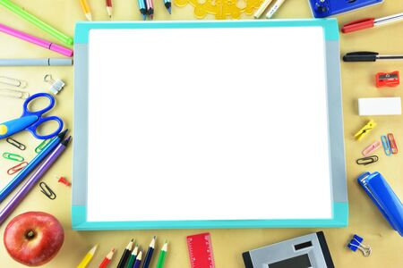 Whitebord and school supplies on wooden background Фото со стока