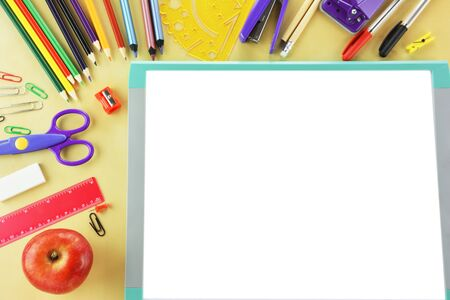 Blank whitebord and school supplies on wooden background Фото со стока