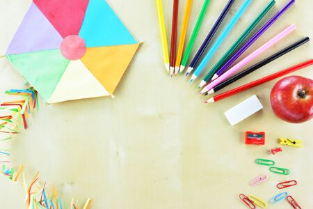 Colored paper kite and school supplies on wooden table