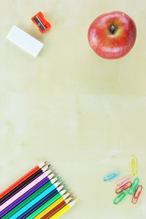 Colored pencils, rubber,sharpener,colored paperpens and an apple on wooden table Standard-Bild