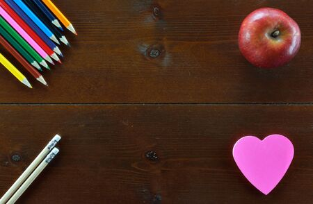 Colored pencils,pencils,an apple and  a heart shaped note sticker on wooden table