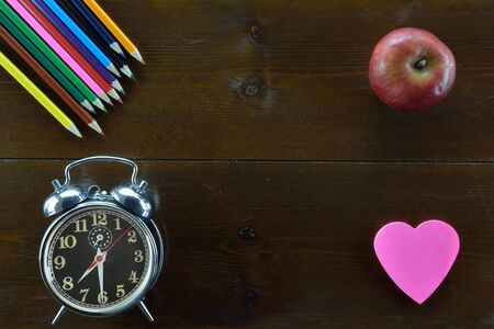 Colored pencils,alarm clock, an apple and  a heart shaped note sticker on wooden table
