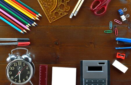 Colored pencils,pencils,scissor, rubber,sharpener, paperclip,rulers,pens,note blank paper,stapler calculator, and alarm clock on wooden table