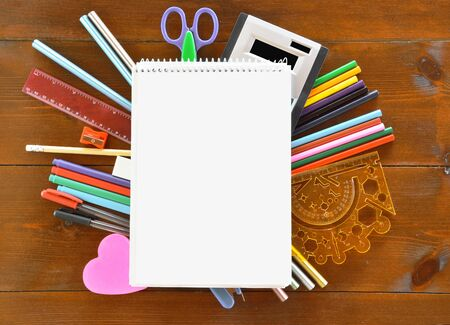 Blank spiral-bound notebook and school supplies on wooden  table