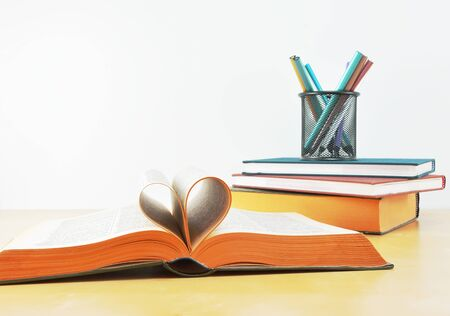 Love school concept with book pages formed into heart shape,books and  pencil holder with colored pencils