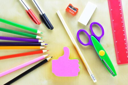 Thumps up shaped note sticker,colored pencils,rubber,sharpener,scissor,pens, ruler on wooden table Фото со стока