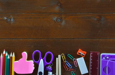 School supplies on dark colored wooden table Фото со стока