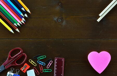 School supplies and heart shaped note sticker on dark colored wooden table