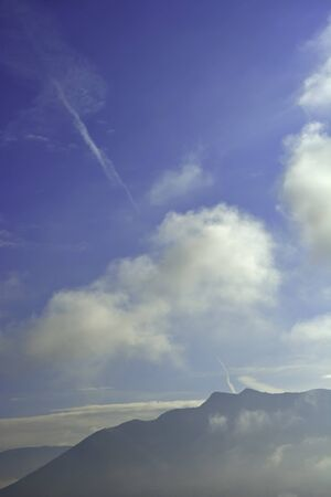 Scenery with mountain surrounded by clouds and fog Stock Photo