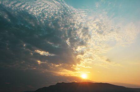 Sun shining through dramatic cloudscape over the mountain Stock Photo