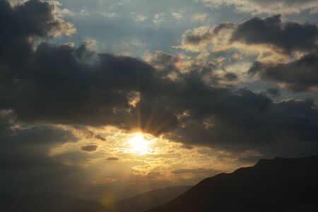 Sun shining through clouds over the mountain Stock Photo