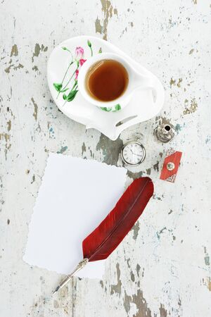 Quill pen with deep red feather, quill stand,a blotter,a blank paper ,an old pocket watch,and tea cup with matching saucer on old wooden table