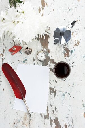 Quill pen with deep red feather, quill stand,a blank paper ,an old pocket watch, a bouquet of white chrysanthemums, coffee maker and cup of black coffee  on old wooden table