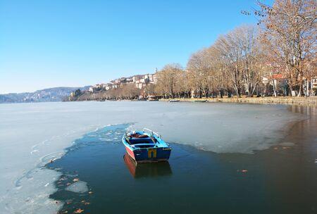 Fishing boat in frozen lake Orestiada in Kastoria, Greece