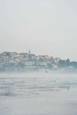 Town  and lake of Kastoria covered with snow and ice and  some birds  flying some others standing at frozen lake