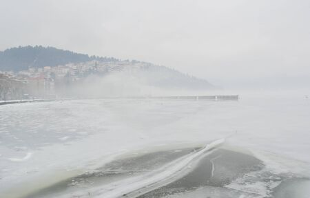 Winter scene with the frozen lake Orestiada in Kastoria,Greece a dull ovecast misty day Imagens