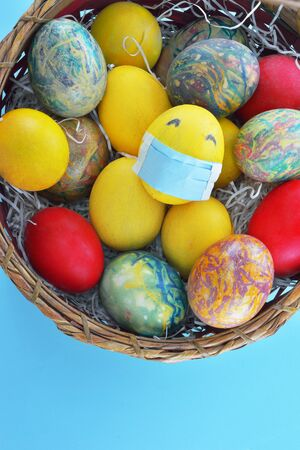 Basket with colorful eggs and a yellow egg with protection mask on light blue background
