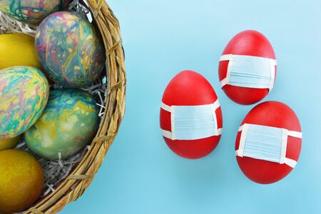 Basket with colorful eggs and red eggs with protection masks beside on light blue background