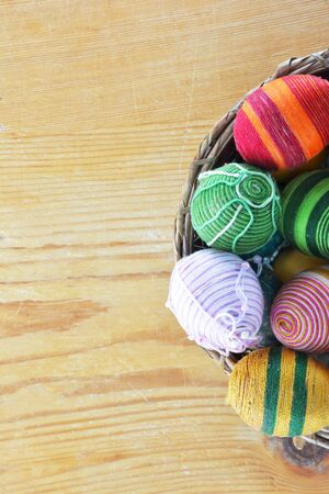 Eggs decorated with threads on wooden table