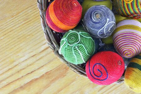 Basket with eggs decorated with threads on wooden  table