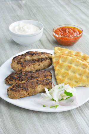 Kebabs with pita bread, choped onion , yogurt and tomato saucei n bowls on wooden table