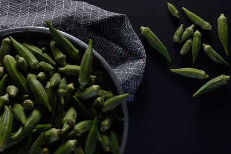 Okra in colander ,a kitchen towel and some okra laying out on black background