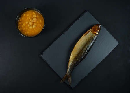 Chickpea soup and smoked herring on black background