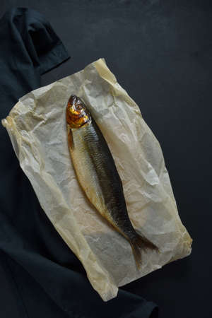 Smoked herring on black towel and baking paper