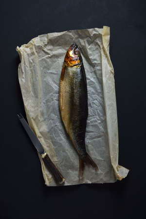 Smoked herring on baking paper and knife on black background