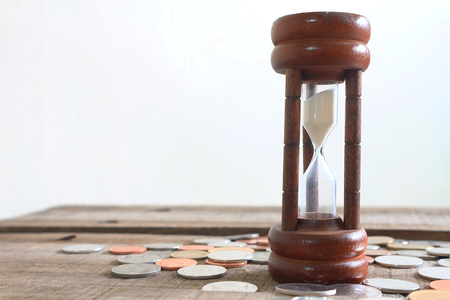 Hourglass and coins on wood plate , financial concept