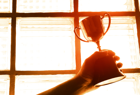 Winner show trophy with bright light form window background.